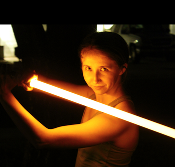 A woman holding a bright orange lightsaber that illuminates her face, arms and upper torso.