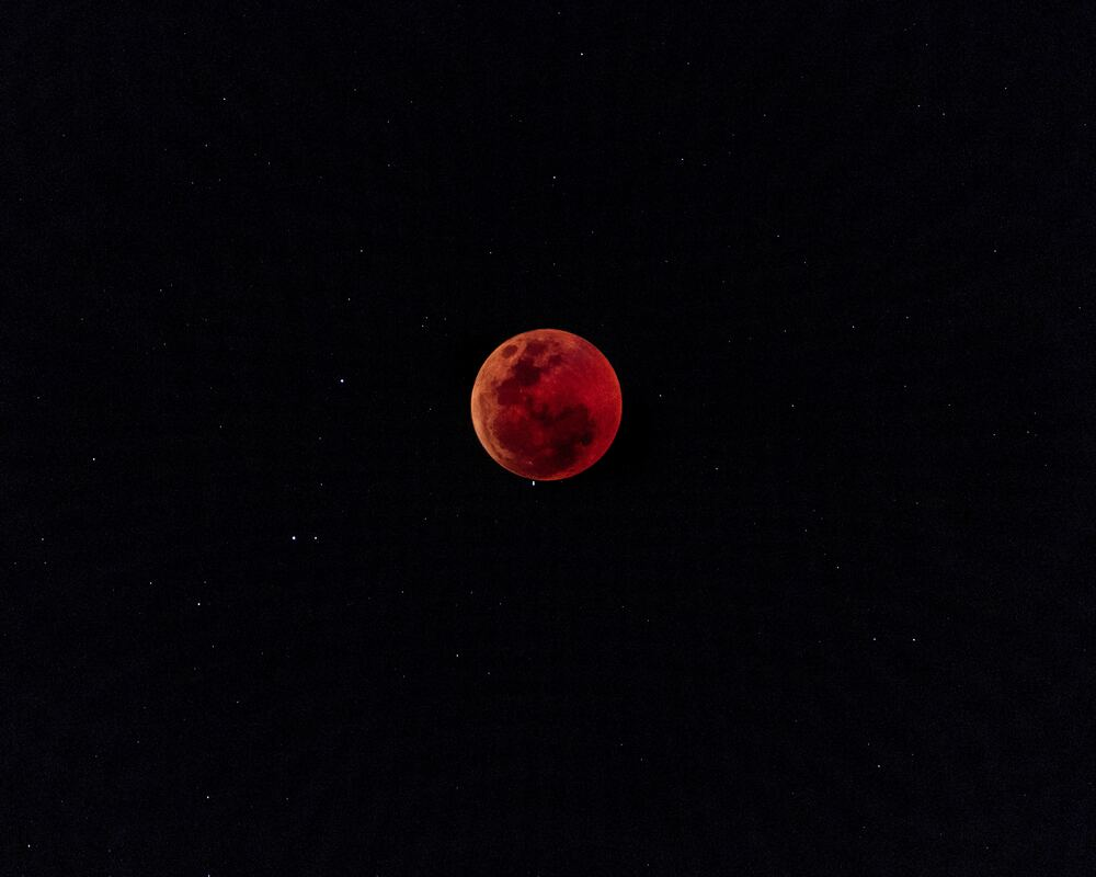Blood-red moon hanging in night sky with stars.