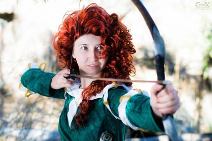A red-haired woman in a green dress, preparing to loose an arrow from a bow.